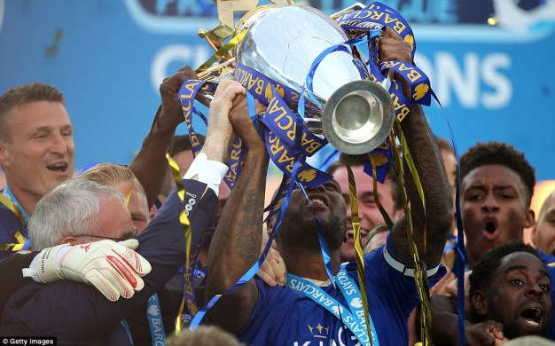 The Leicester skipper proudly lifts the Premier League trophy at the King Power Stadium after easing to victory against struggling Everton