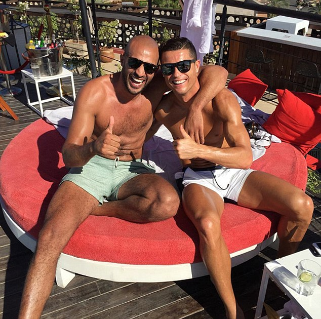 Cristiano Ronaldo's kickboxer friend, Badr Hari, has reportedly been arrested by police over an alleged hotel assault. Ronaldo (right) and Hari (left) are pictured relaxing in the sun