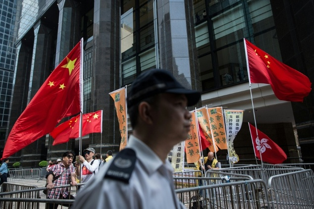 A policeman walks past pro-China supporters in Hong Kong on May 18, 2016, during the second day of a visit by China's National People's Congress (NPC) Standi...