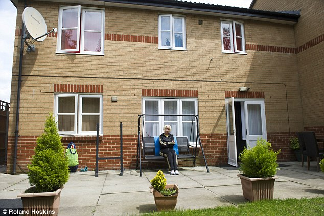 New life: Barci's wife Mimoza Barci showing off the family's four-bed housing association house. They posed as Kosovan refugees to gain British citizenship and have lived rent free in the £560-a-month property