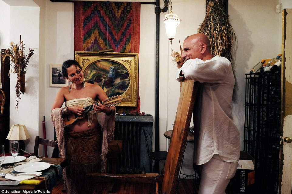 Michel watches a woman playing guitar as he prepares to sit down for dinner with his lover and a pair of Polyamorous ladies