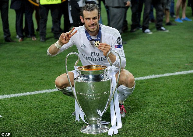Gareth Bale poses with the Champions League trophy after winning it for a second time with Real Madrid