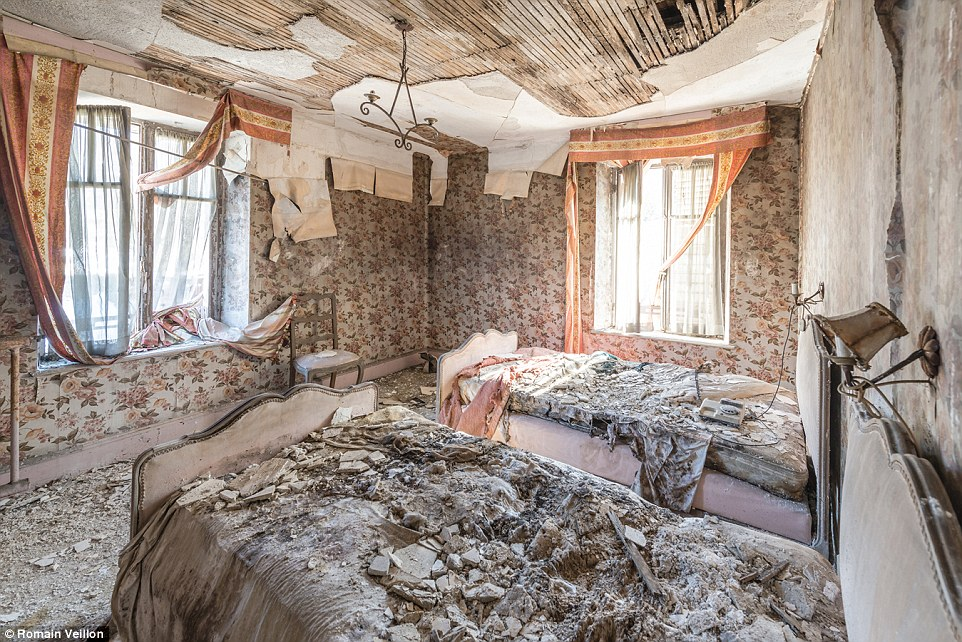 In this old home in France, the ceiling and walls have started to fall apart and cave in, leaving debris all over the beds and floor