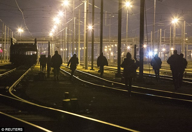 Migrants walk on the railway tracks leading to the entrance of the Channel Tunnel.