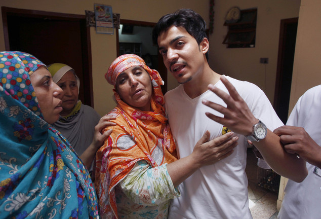 Family members comfort Hassan Khan, center, the husband of Zeenat Rafiq,  at his home in Lahore, Pakistan
