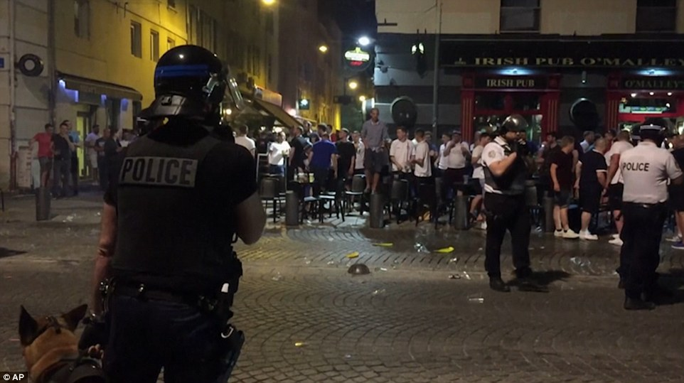 England fans huddle together outside the Irish bar as police dog units and riot officers watch on in the Old Port area of the city