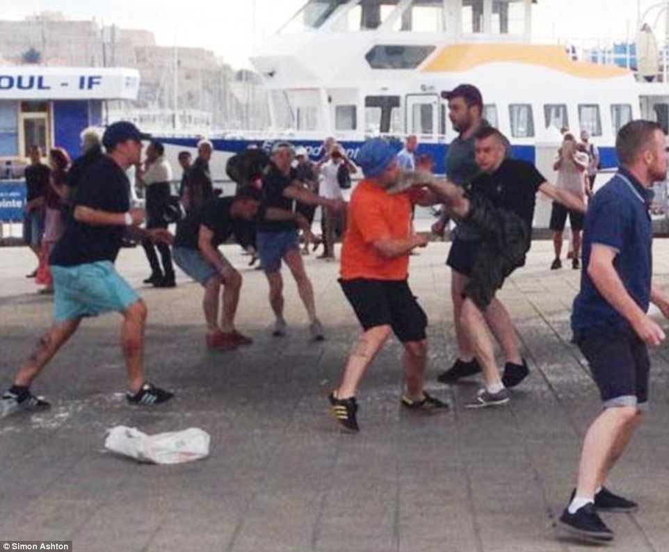 The fan, who was later dunked into the sea, receives a kick to the face as he clashes with Russian hooligans earlier in the day