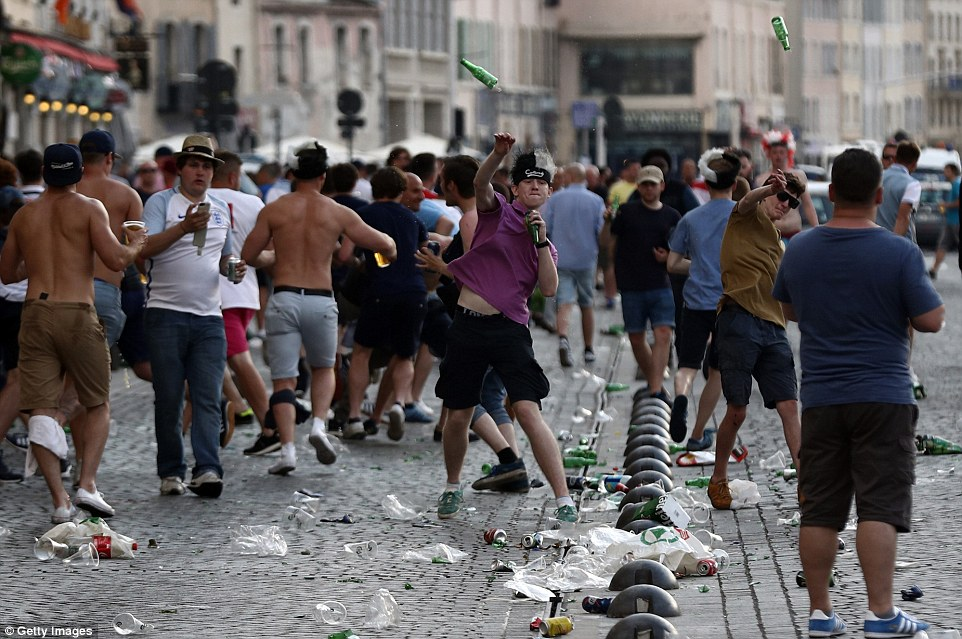 Drunken English fans are captured hurling bottles at police and other fans during the violent clashes in the Old Port district of Marseille