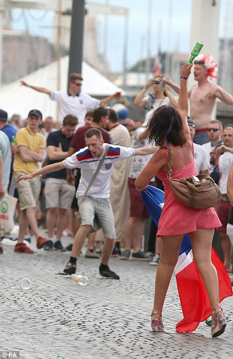 Pictured, a French woman goes to throw a bottle at English fans