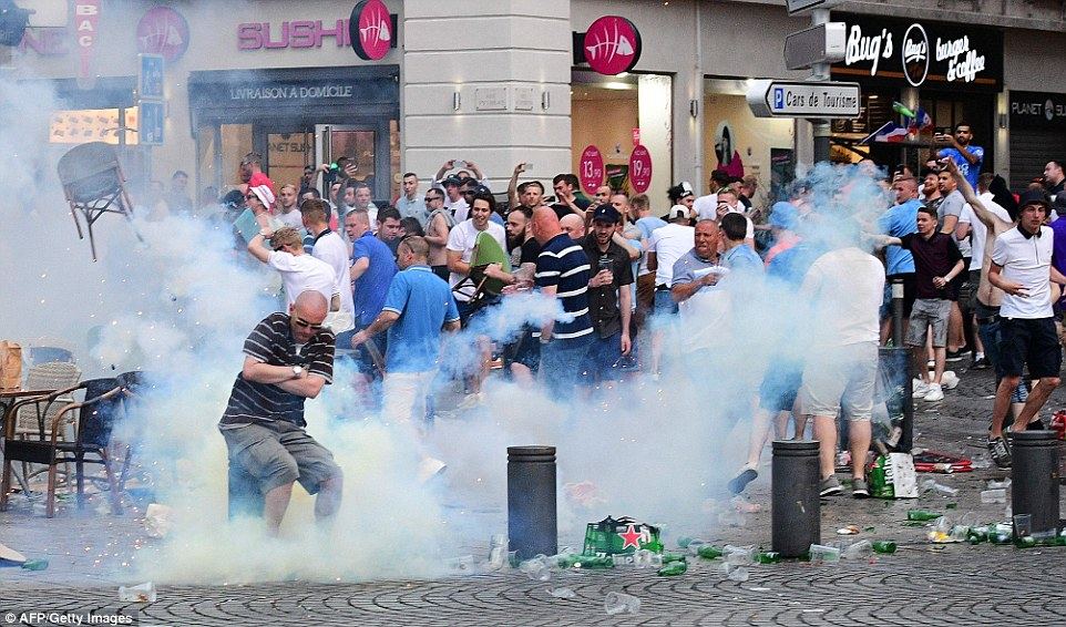 England fans hurl chairs at French police as tear gas is fired outside bars to disperse crowds who had been clashing with Russian supporters and police