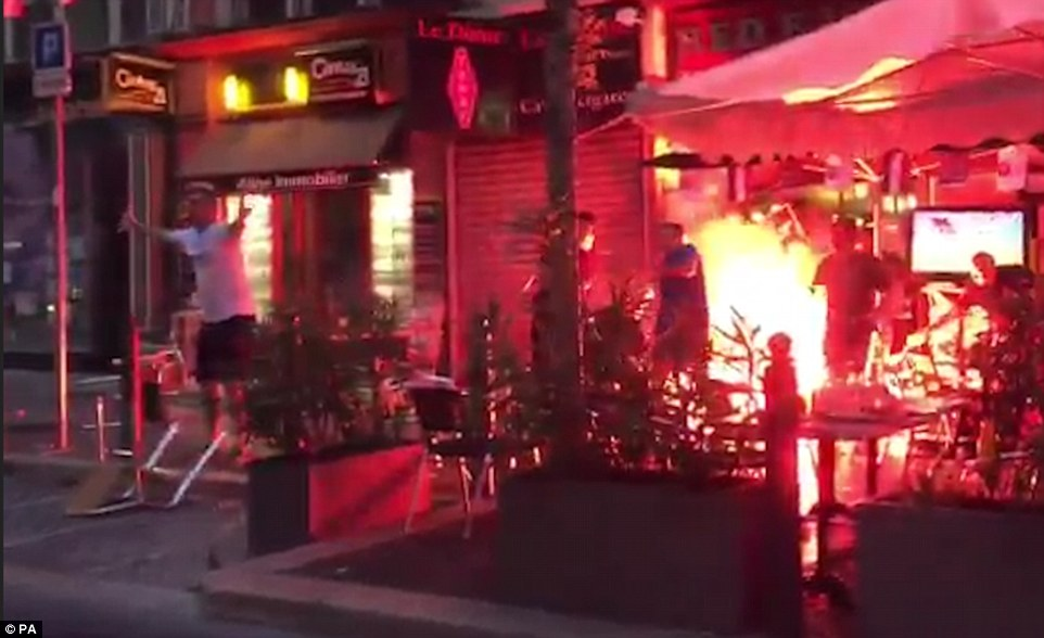 A cafe is engulfed in flames as English fans are targeted while drinking on the terrace of cafe on the streets of Marseille's Old Port