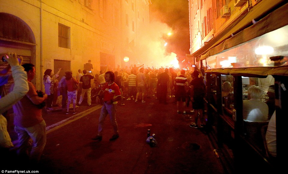 A flare is let off as fans gather outside a pub in the Old Port, where they had spent the day drinking and chanting prior to England's opening Euro 2016 match against Russia