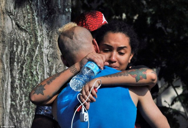 Friends and family members embrace outside the Orlando Police Headquarters during following the shooting at Pulse nightclub