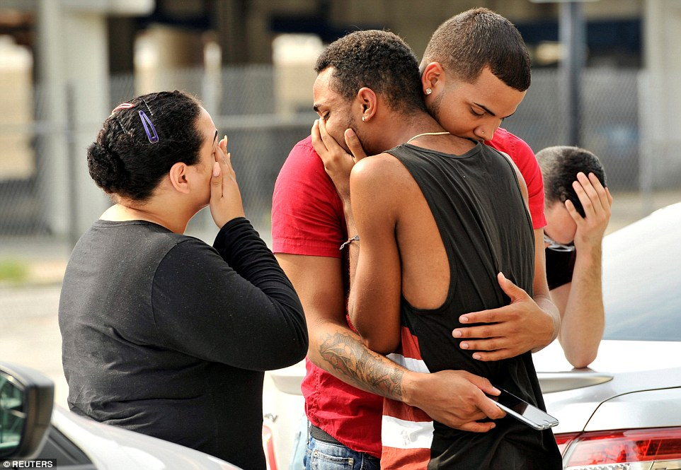 Friends and family members embrace outside Orlando Police Headquarters following the deadly shooting in the early hours of this morning