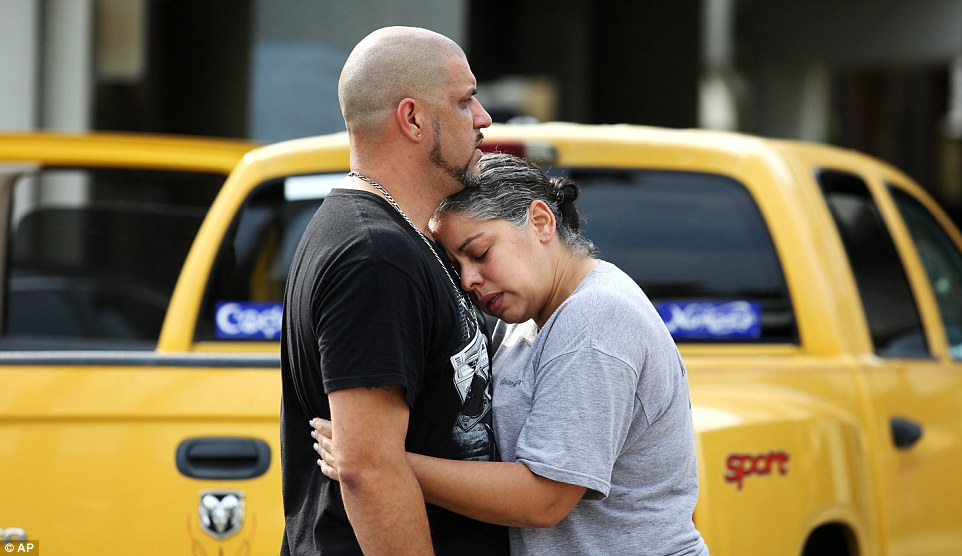 Ray Rivera, a DJ at Pulse Orlando nightclub, is consoled by a friend outside of the Orlando Police Department following the shooting