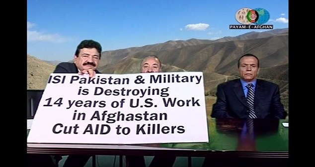 Seddique Mateen is an Afghan man and also hosts the Durand Jirga Show on a channel called Payam-e-Afghan, which broadcasts from California. Pictured: Mateen (left) holds up a sign to camera