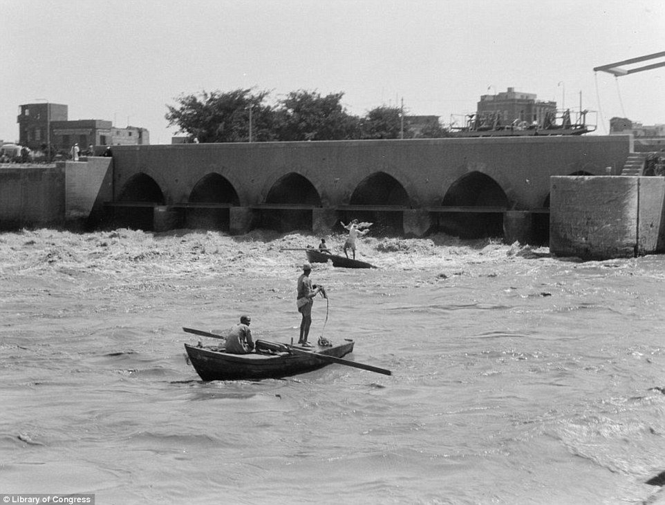 In this photograph taken in 1934, fishermen cast their nets into the Nile water as it gushes around them