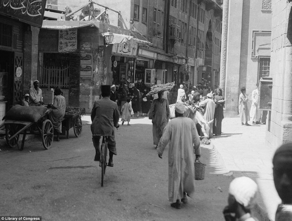 Another shot of a busy street, taken in 1934, shows a trader walking with his goods on a tray on top of his head