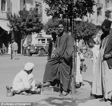 Another man gets his shoe shined on the side of the road, also pictured in 1934
