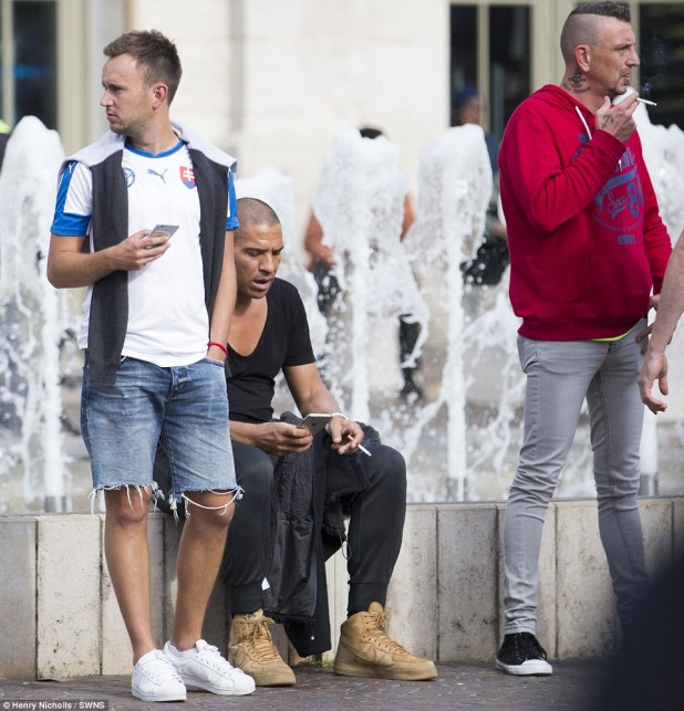 By-stander: Stan Collymore (centre) was seen sitting down and using his mobile phone after being caught up in the tear gas used by French police