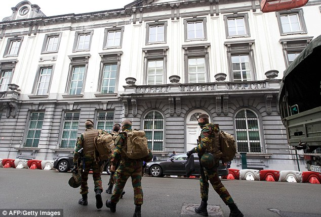 Belgian soldiers walk the streets of Brussels today after a suspected terrorist cell was dismantled overnight. Suspects were seen scoping out a fanzone where today fans will watch Belgium's game against Ireland