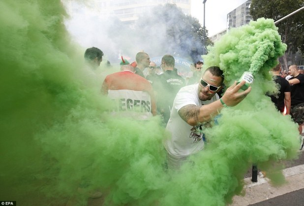 A fan unleashes a green 'smoke bomb' before the match - one of the colours on his nation's flag