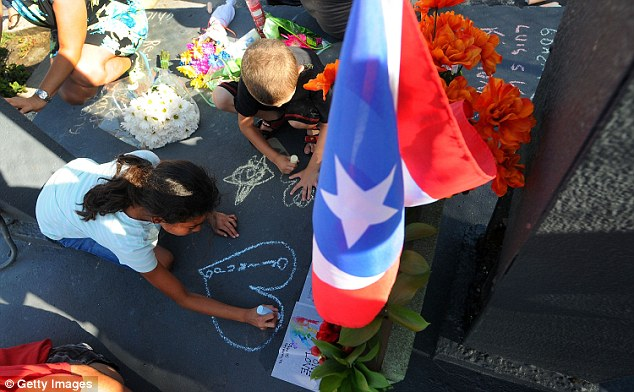 Children write messages for the victims of the Pulse Nightclub shooting at a makeshift memorial at the scene. The memorial is decorated with a Puerto Rican flag as many of the victims were originally from Puerto Rico