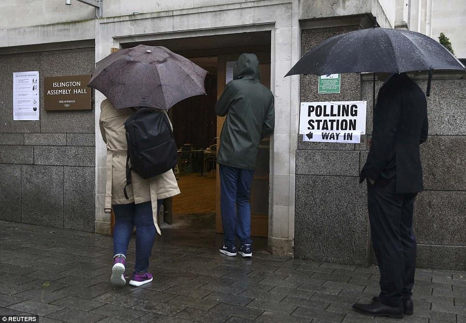 día histórico: Los votantes en Islington, al norte de Londres, llegan a votar como urnas para el referéndum de la UE abrió hoy como Gran Bretaña finalmente consigue algo que decir sobre si quedarse o irse -, pero el mal tiempo podría golpear participación