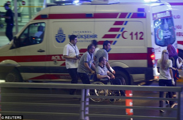 Ambulance crews ferry the wounded away from the terminal. The wounded are believed to include a number of police officers and security personnel