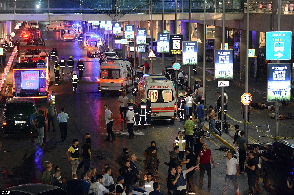Shocked crowds of bystanders and holidaymakers mix with emergency services crews outside the terminal where the attackers struck