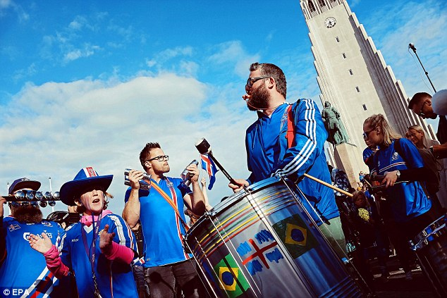 A fan bangs a drum decorated with the flags of Iceland and Brazil - a team Iceland could meet at the World Cup