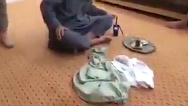 The video was captured on the phone of a dead ISIS terrorist, according to Radio Sawa, who say the clothes belong to the seated man's friend who is carrying out the rape