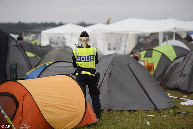 A police officer helps with security in the campsite at Bravalla Festival in Norrkoping, Sweden, on Saturday. Swedish police told the media that they are investigating five cases of alleged rape and more than a dozen suspected sexual assaults committed at the Bravalla Festival over last weekend