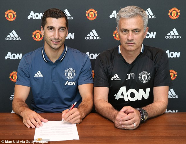 Mkhitaryan sits next to new boss Jose Mourinho after signing his four-year deal at Old Trafford