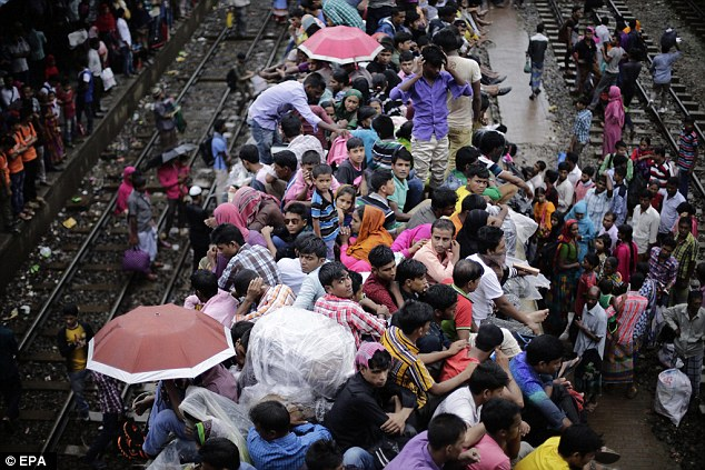 Travelers sit atop an overcrowded train as they travel to their villages ahead of the Eid Al-Fitr celebrations at the Airport Railway Station in Dhaka, Bangladesh, a day before the latest attrocities