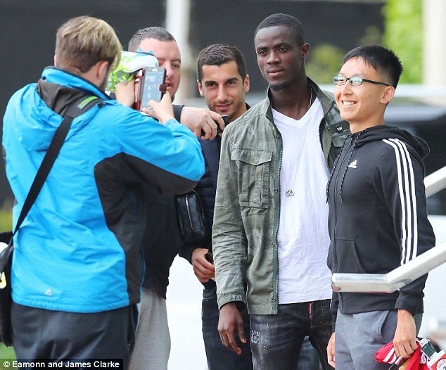 Henrikh Mkhitaryan (left) and Eric Bailly pose with fans desperate to get a photograph with the new signings