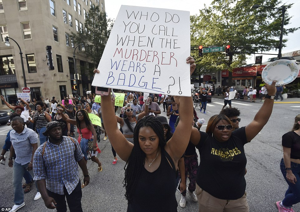 'Who do you call when the murderer wears a badge?' An estimated 5,000 people halted traffic as they demanded justice for black men killed at the hands of police officers