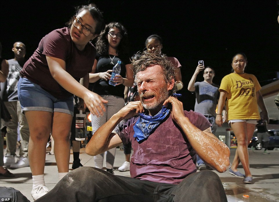 A protester gets help after being knocked to the ground after being pepper sprayed by police as marchers numbering nearly 1,000 take to the streets to protest against the recent fatal shootings of black men by police