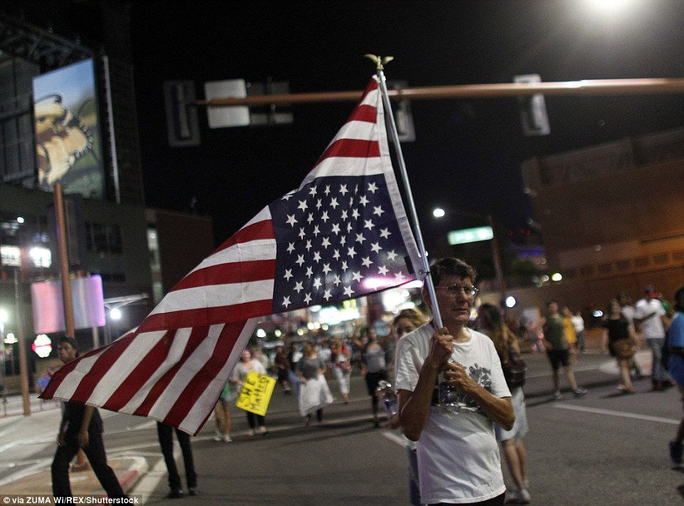 In Rochester, New York, the SWAT team arrived and police arrested 74 protesters who were blocking the streets (pictured, one demonstrator in Phoenix holding the flag upside down, a signal for dire distress)
