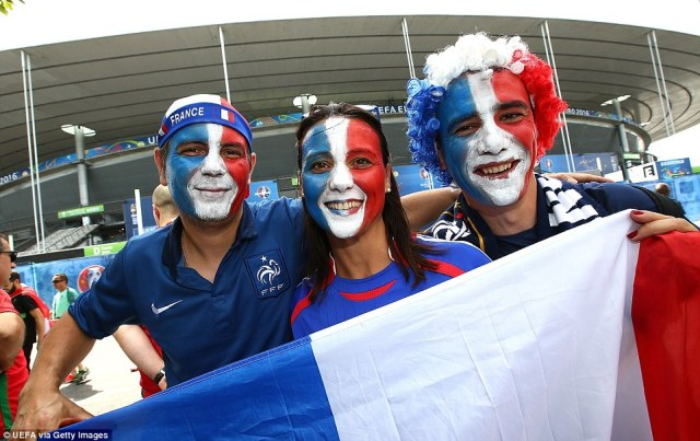 Getting ready: Fans with French flags painted onto their faces gather outside the stadium ahead of the game between Portugal and France