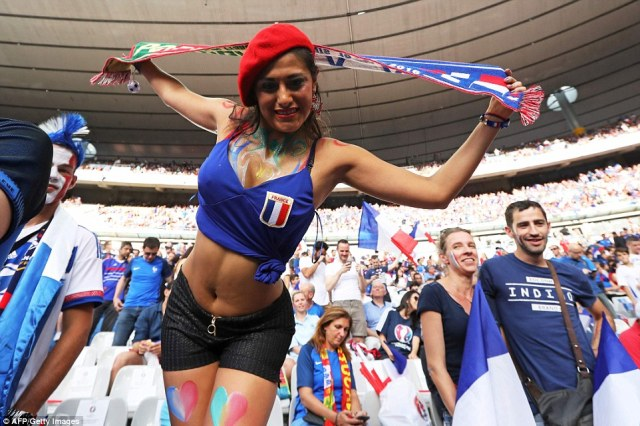 A France fan wearing a red beret holds up a scarf as she poses for a photo in the Stade de France as Portugal take on the host nation