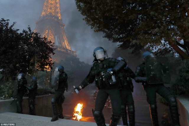 French riot police reacted with tear gas after clashes broke out near the Eiffel Tower at the Paris fan zone during the Euro 2016 final