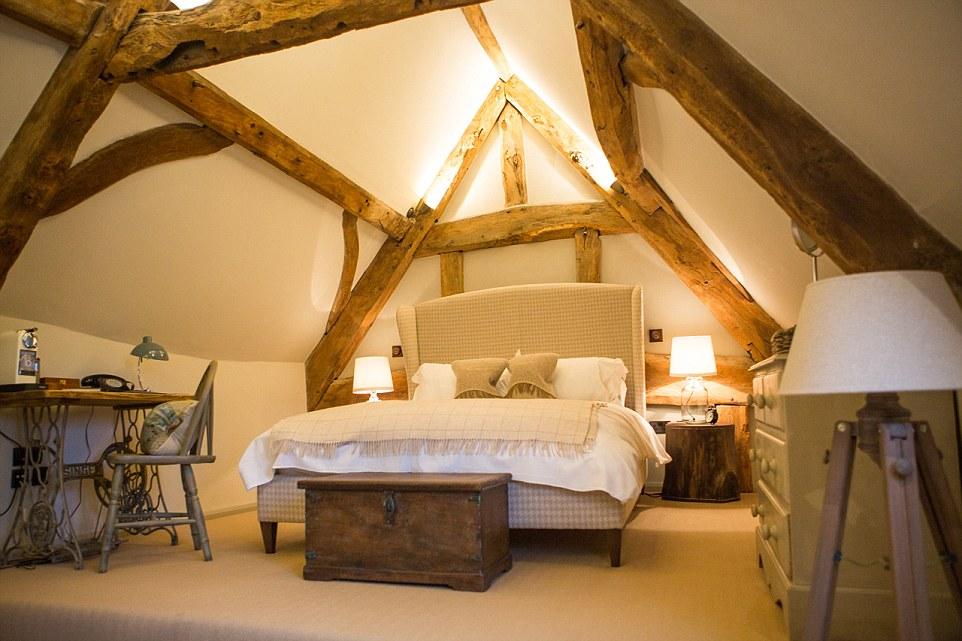 Questa forma di una stanza al piano superiore con travi a vista e mobili d'epoca o recuperato, tra cui un tavolo fatto da una macchina da cucire