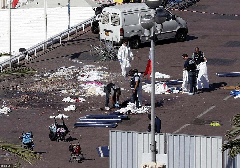Horrible: equipos policiales y forenses inspeccionan los cuerpos en la luz del sol francesa donde al menos diez muertos y 50 heridos - muchos de ellos en sillas de paseo dejado abandonado hoy