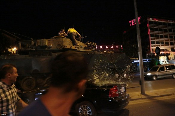 A tank in central Ankara drove over a car as protesters clambered aboard preventing it from moving across the city in Turkey's coup
