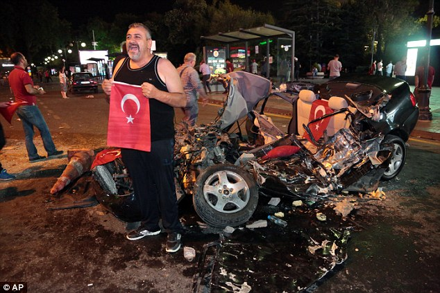 A man poses with the flag of Turkey in front of a car crushed by a military tank as people gather in Kizilay Square to protest the military coup in the capital city of Ankara