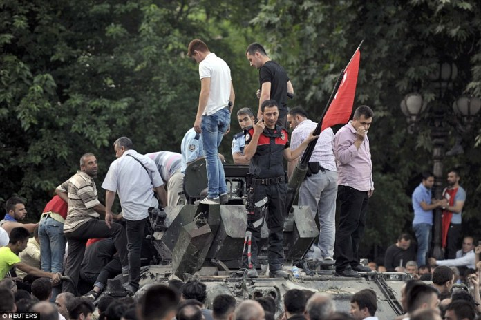 A Turkish policeman and other people stand atop of a military vehicle in Ankara after crushing the rebellion