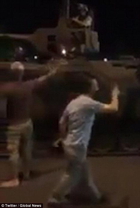 Pictured, men shout at soldiers in tanks on the streets of Ankara