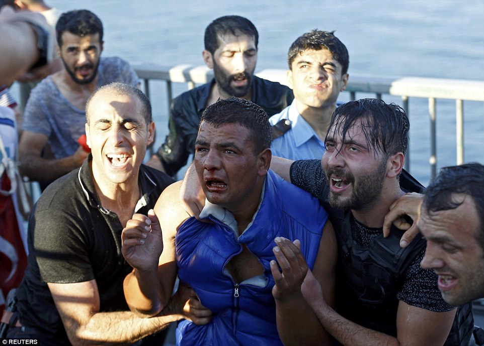 Police officers arrest a soldier after he was attacked by a mob of civilians following the surrender of 100 rebels on Bosphorus Bridge in Istanbul