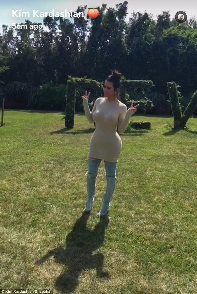 Peace out: Kim Kardashian wore a tight beige dress with over-the-knee, ripped denim boots as she arrived at the Revolve party in The Hamptons on Saturday